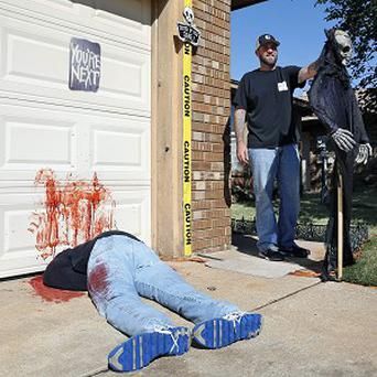Johnnie Mullins poses with his controversial Halloween display featuring headless dummies, at his home in Oklahoma. (AP Photo/Sue Ogrocki)