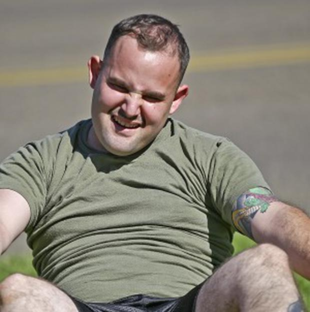 An overweight service member who failed a fitness test struggles to do sit-ups during a workout, at the Marine Corps Recruit Depot in San Diego (AP)