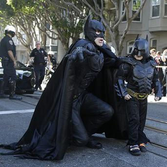 Miles Scott, dressed as Batkid, right, walks with Batman before saving a damsel in distress in San Francisco (AP)