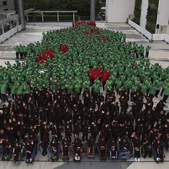 Dressed in red, green and black hoodies, 852 Thai students gather together to break the Guinness World Record for forming the largest human Christmas tree (AP)