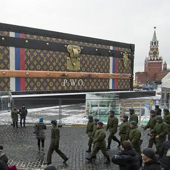 Tourists and visitors pass a two-storey Louis Vuitton suitcase erected in Red Square, Moscow (AP)