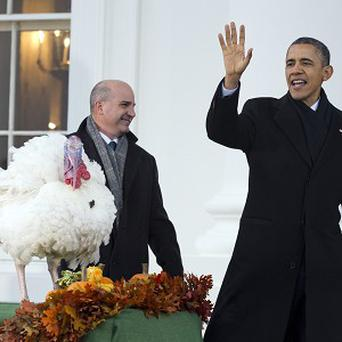 President Barack Obama waves after carrying out the Thanksgiving tradition of saving a turkey from the dinner table with a