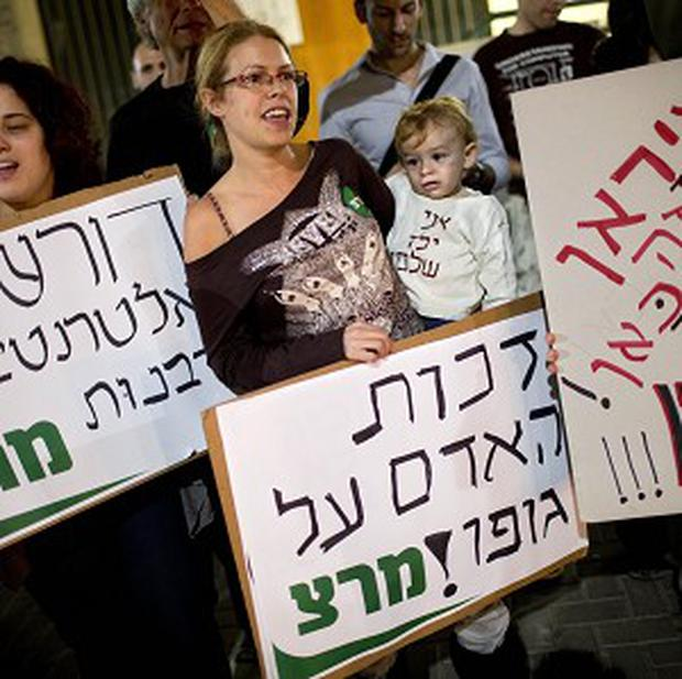 Israelis protest in support of a woman who was fined after refusing to have her son circumcised, in Tel Aviv, Israel (AP)