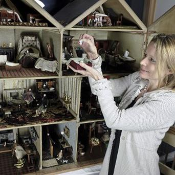 Auctioneer Catrin Hampton checks miniature china from the doll's house which fetched tens of thousands of pounds