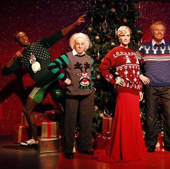 Wax figures in Christmas jumpers at Madame Tussauds in London.