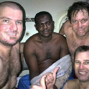Harrison Odjegba Okene inside a decompression chamber with members of the DCN Diving team who saved his life after being trapped for three days underwater (AP/DCN Diving)