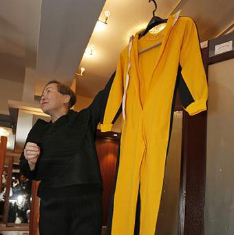 Anna Lee, vice-chairman of Spink auction house, holds Bruce Lee's original yellow jumpsuit that he wore in Game Of Death, his last film. (AP/Vincent Yu)