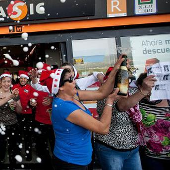 Workers of a petrol station celebrate after winning the second prize of the Christmas lottery El Gordo in Tenerife (AP)