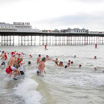 Members of the public head into the freezing sea for the annual Brighton Swimming Club Christmas Day swim