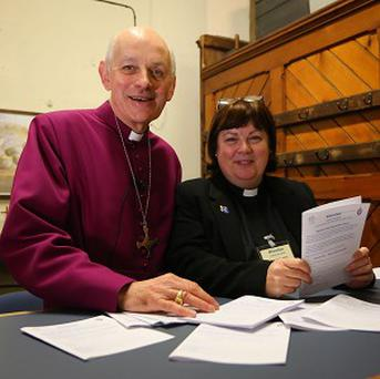 The Bishop of Dover, the Right Reverend Trevor Willmott, with the Assistant Curate of All Saints Church in Murston, Lesley Jones, stand behind the counter of the Murston Community Bank