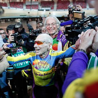 French cyclist Robert Marchand, aged 102, celebrates with fans after beating his record for distance cycled in one hour (AP Photo/Thibault Camus)