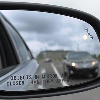 A side mirror warning signal in a Ford Taurus at a car testing area in the US (AP)