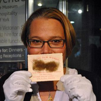 York Castle Museum history curator Alison Bodley with what experts believe is the worst Valentine's Day card in history (York Castle Museum/PA)