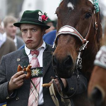 A man wearing the traditional costume of the region eats a Bavarian pretzel in Bad Tolz, southern Germany (AP)