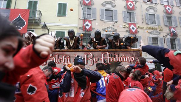 People wearing costumes and protective helmets throw fruit as part of the traditional Battle of the Oranges in the northern Italian town of Ivrea. (AP)