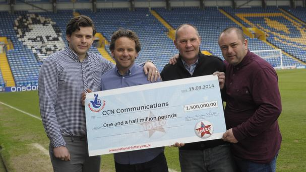 Lewis Fox, Tom Fox, Mark Bush and Sid Veness they celebrate their jackpot win at Fratton Park, Portsmouth (Camelot/PA)