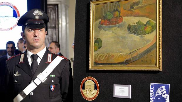 An officer stands by the stolen Paul Gauguin still life recovered by authorities. (AP/Daniele Leone, Lapresse)