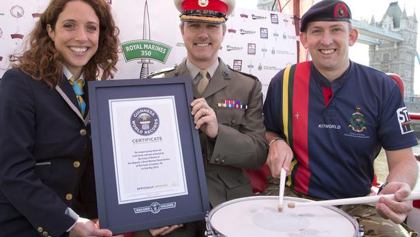 Anna Orford from Guinness World Records presents Lieutenant Colonel Nick Grace, centre, with the drum roll world record certificate, with Corporal Bugler Stu Warmington (Ministry of Defence/PA)