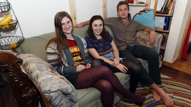 Lara Russo, Cally Guasti and Reese Werkhoven sit on the couch in their flat, after returning the cash they found inside it (AP)