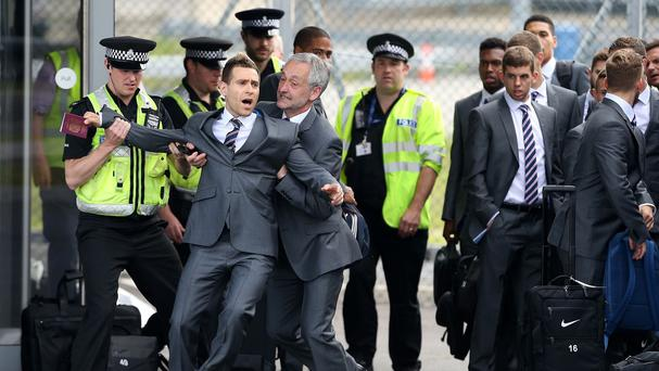Comedian Simon Brodkin is taken away from the England team by security at Luton Airport