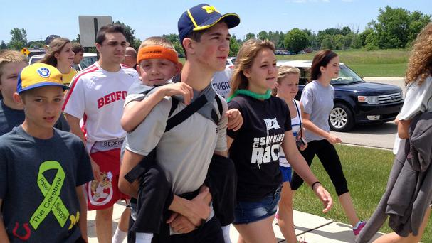 Hunter Gandee, 14, walks during the Cerebral Palsy Swagger to raise awareness for the muscle disorder that affects his seven-year-old brother, Braden, who was on his brother's back for the entirety of their 40-mile journey (AP)