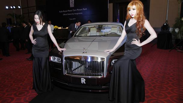 Models pose beside a Rolls-Royce Wraith during the inauguration of its official dealership in Phnom Penh, Cambodia, which will open next month (AP)