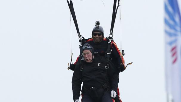 Former president George Bush prepares to land after celebrating his 90th birthday with a tandem parachute jump (AP)