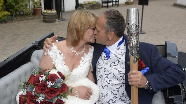 Damone Barnes and Sally Eastmond take the baton ahead of their wedding ceremony in Gretna (Ben Birchall for Glasgow 2014/PA Wire)
