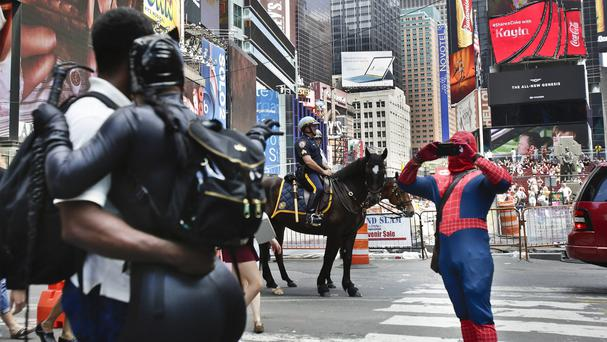 A Times Square visitor poses for photos with an iconic costumed character but they could soon face a crackdown (AP)