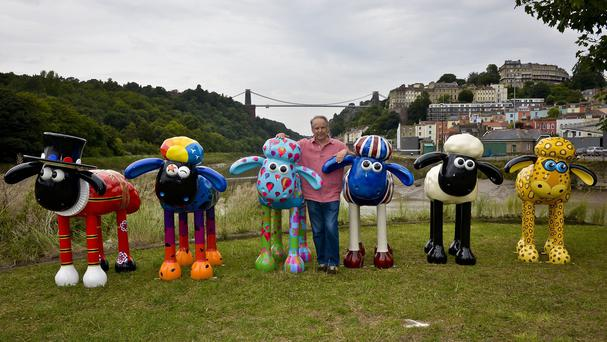 Creator Nick Park with giant sculptures of Shaun the Sheep as they stand before Brunel's Clifton Suspension Bridge, Bristol, to launch a new public arts trail