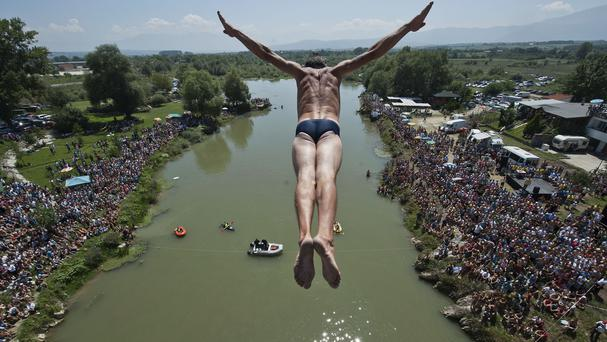Spectators watch as a diver Sali Riza Grancina performs the winning jump from the Ura e Shenjte bridge during a traditional high diving competition in Kosovo (AP)