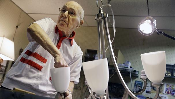 Herman Goldman, 101, refurbishes a light fixture in his workshop at Capitol Lighting, New Jersey (AP)