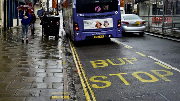 A bus passes a stop in Bristol which has had its road marking spelled incorrectly