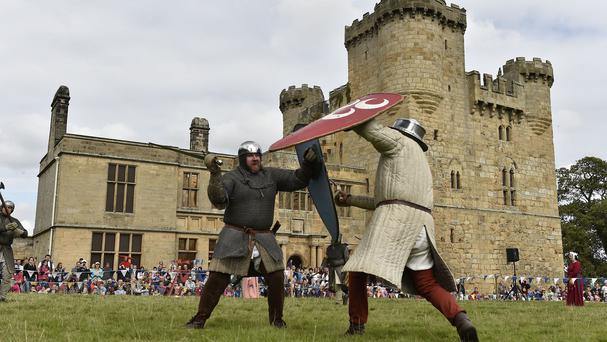 Knights battle with each other during a re-enactment of a medieval tournament at Belsay Castle in Northumberland