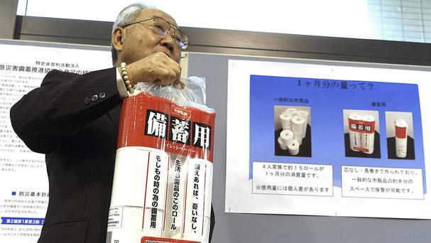 Satoshi Kurosaki shows the emergency stock of toilet paper at the Ministry of Economy, Trade and Industry in Tokyo. (AP)