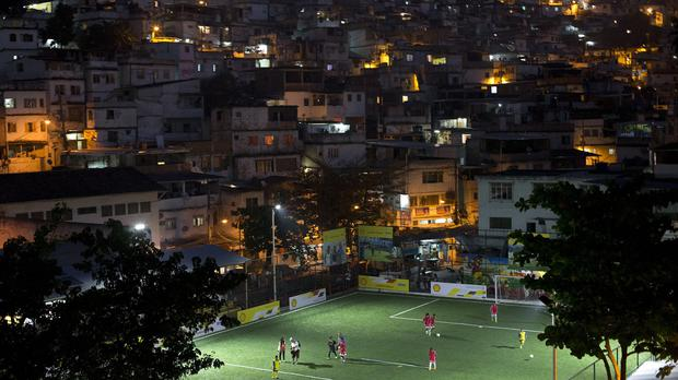 Residents of the Morro da Mineira favela play in the newly installed football pitch powered by player's footsteps, in Rio de Janeiro, Brazil (AP)