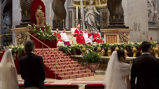 Newly married couples attend a wedding ceremony led by the Pope in St Peter's Basilica