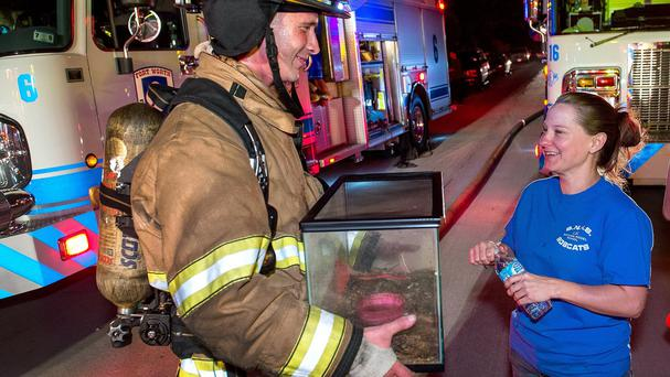 Firefighter Craig Tipton reunites Jamie Wilson with the family's pet frog (Fort Worth Fire Department/AP)