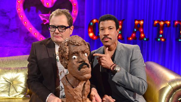 Lionel Richie with Alan Carr, who is holding an unflattering likeness of the singer (Channel 4/PA)