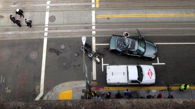 Police look over a car with a caved-in roof after a window cleaner fell at least 11 storeys on to the moving vehicle in San Francisco (AP)