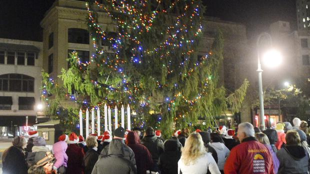 Unimpressed residents look on as the spindly 50ft Christmas tree is lit up in Reading, Pennsylvania (AP)