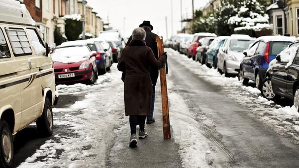 A woman uses a plank of wood to help keep her balance on an icy road