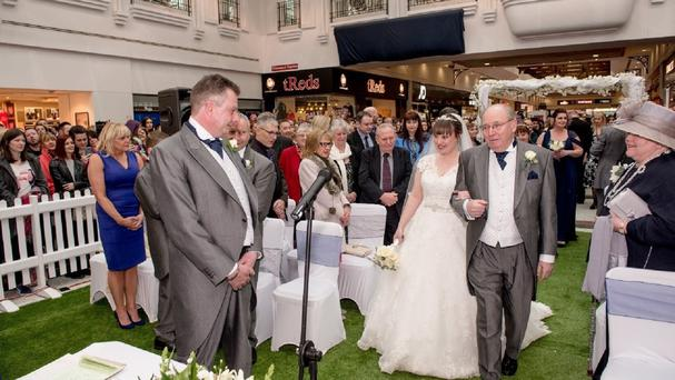 Kate Marr with her father Peter Butterworth, walking to her wedding ceremony to Mike Davies (left), at Telford Shopping Centre, Shropshire, where the couple met and fell in love. (Telford Shoping Centre )