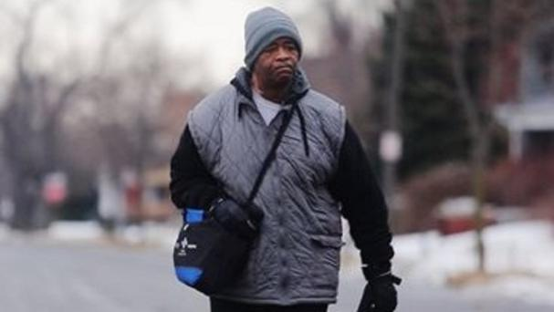 James Robertson walks to catch his morning bus in Troy before walking to his job at Schain Mold & Engineering in Rochester Hills (AP/Detroit Free Press, Ryan Garza)