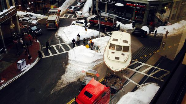 A broken-down truck towing a 43ft yacht makes waves in Boston's financial district (AP)