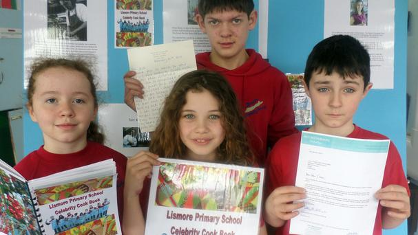 Lismore Primary School pupils holding their charity cookbook, which has turned into a who's who of British cookery after recipes were donated by Delia Smith, Michel Roux Jr and Marco Pierre White (Lismore Primary School/PA)