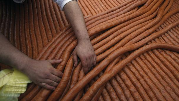 A cooks sells the giant sausage at the Sausage Festival in Turija, Serbia (AP)