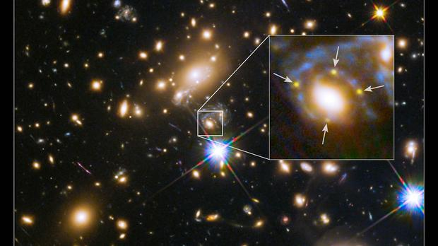 A large cluster galaxy (centre of the box) which has split light from an exploding supernova in a magnified background galaxy into four yellow images (arrows) (Nasa)
