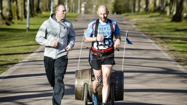 Mike Tindall spurs on fitness fundraiser Rob Edmond pulling a whisky barrel towards the finish line in Wiltshire