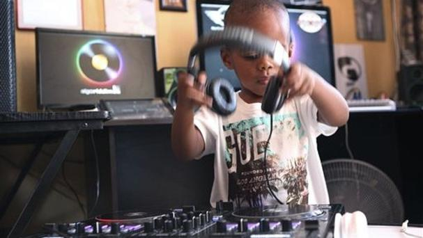 Two-year-old Oratilwe Hlongwane, also known as DJ AJ to his fans, removes his headphones after playing with the buttons and knobs of a sophisticated music system at his home in Johannesburg (AP)